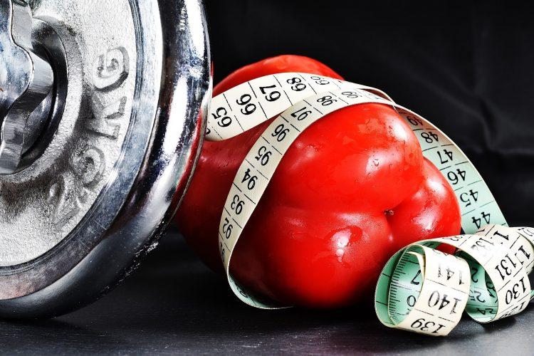פלפל אדום ליד משקולת וסרט מדידה מתוך הפוסט על תזונה לפני ואחרי אימון של ניו אייג סטודיו